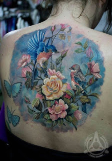 Tatuagem Realista nas costas de rosas, pássaros e borboleta.