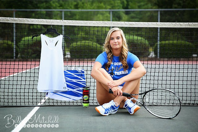 senior girl sitting in front of tennis net holding tennis racket with her uniform hanging on the net