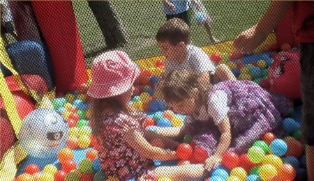 Kids playing with balls in the bouncy house.