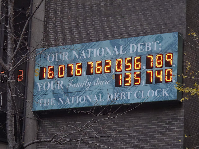 Passing through a huge electronic billboard on a building in Manhattan where it shows the current total USA debt during Autumn 2012 in New York, USA