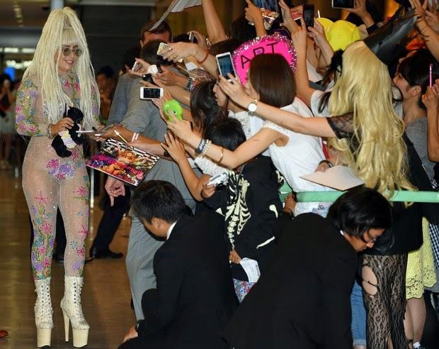 De traje transparente, Lady Gaga cumprimenta fãs ao chegar ao Japão