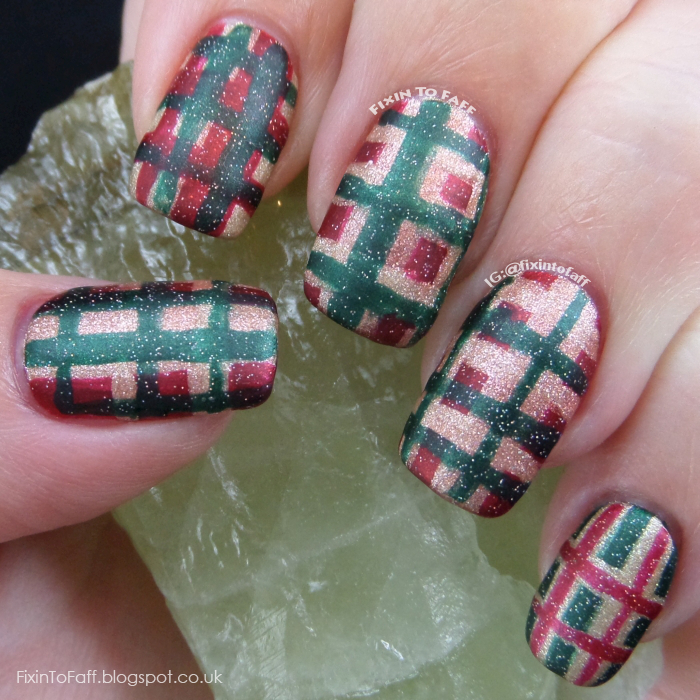 Tartan plaid nail art in Christmas colors red, green, and gold.