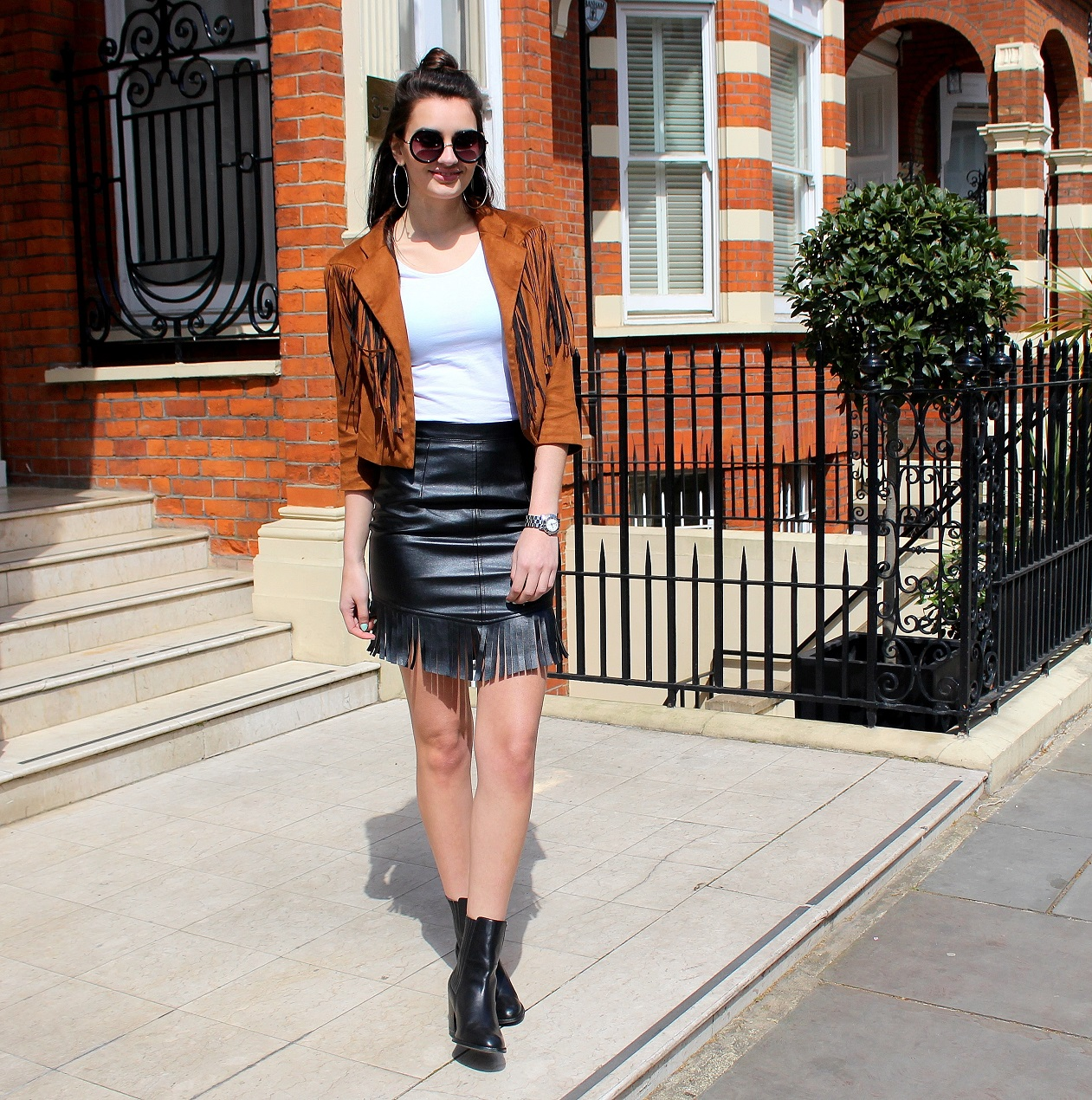 peexo-fashion-blogger-wearing-fringe-jacket-and-leather-skirt-and-boots-and-white-tshirt-and-round-sunglasses-in-spring-70s-inspired