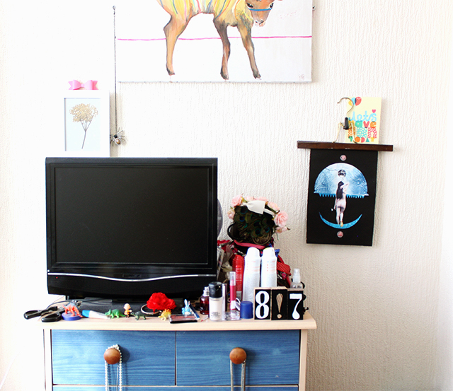 before shot of television and ikea drawers and art on wall