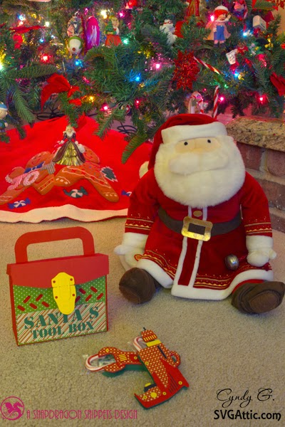 Scene of a stuffed Santa sitting by the tree with his tool box and tools