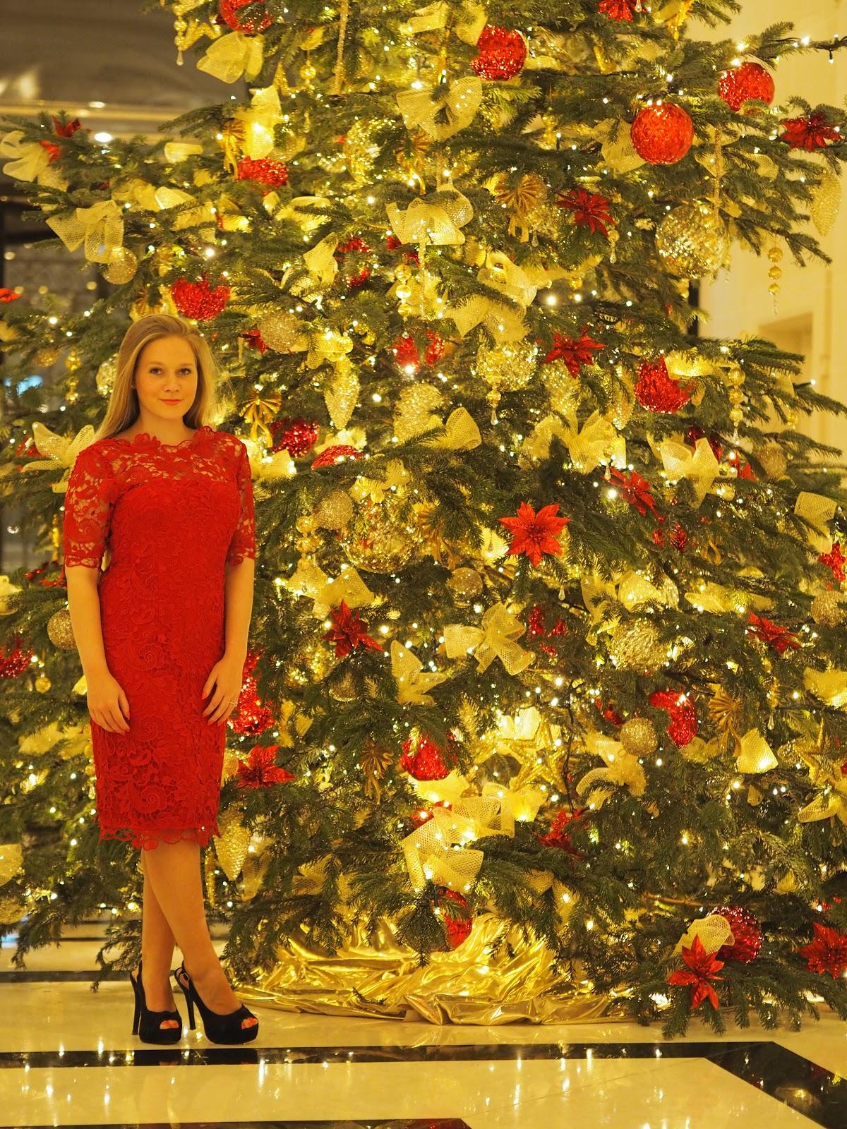 Blonde girl, Katie Matthews, Kalanchoe, standing by Christmas Tree at Peninsula Hotel Paris