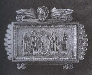 A gold brooch with an applied relief showing a libation scene from the Nimrud Palace reliefs. This is the same as the one worn by Alice Goodall in the portrait above. Has been suggested that the brooch was made by George Goodwin of London, whose registered designs (1873-74) in the Assyrian style conform most closely with this piece. British Museum, I lull Grundy Gift