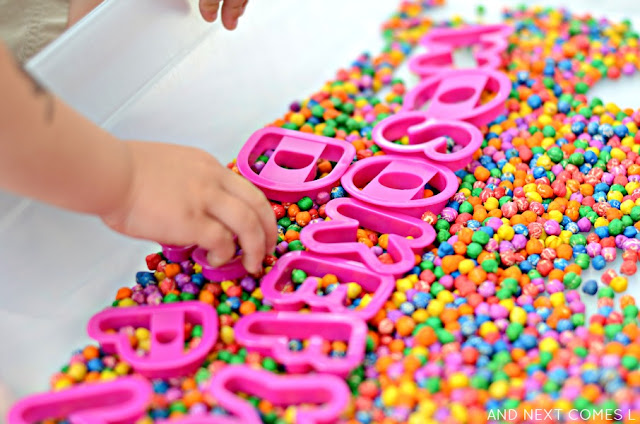 Sensory & literacy activity for kids using rainbow dyed chickpeas and alphabet cookie cutters from And Next Comes L