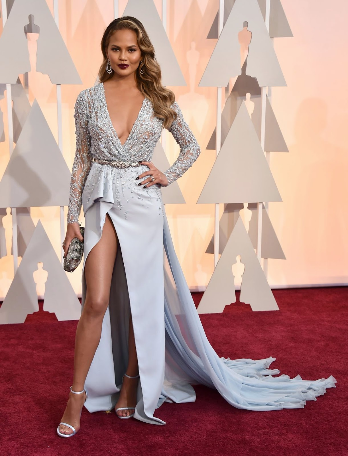 Chrissy Teigen flaunts curves in a plunging gown at the 2015 Oscars in Hollywood