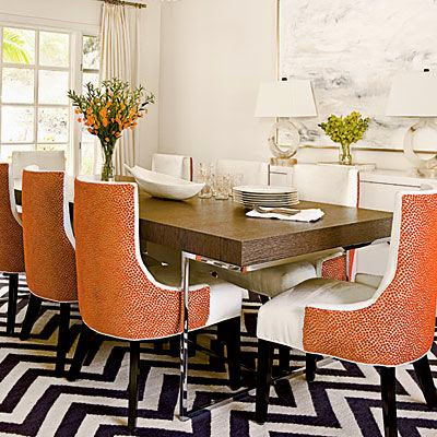 colorful orange chairs in dining room with black white chevron rug
