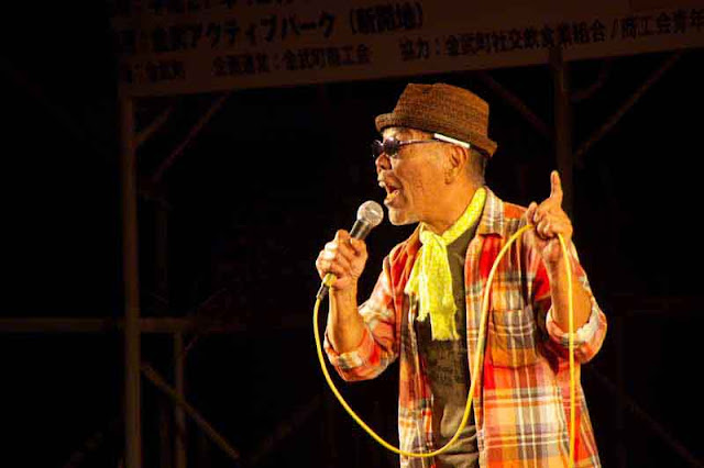 male vocalist, plaid jacket, yellow scarf, brown hat