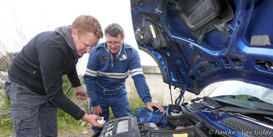 L-R: Grant Blackberry, service crew, Robert Webster, driver, complete their end-of-day checks in Havelock North last night. Petrol Heads entertained local car enthusiasts in Napier Rd, Havelock North, before the Targa Rally cars were serviced and polished, ready for the next stage on Saturday. photograph
