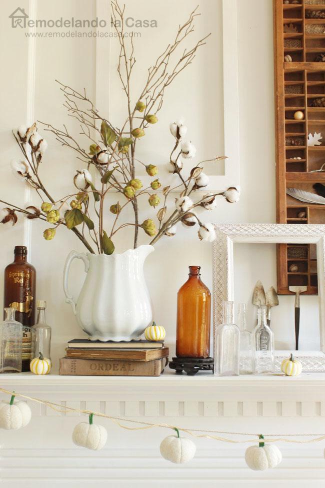 Mantel with felt pumpkin garland, brown bottles, empty frames, white pitcher