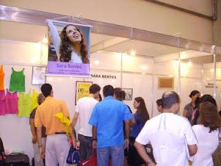 A foto mostra várias pessoas reunidas em frente ao estande de Sara, onde se podem ver camisetas coloridas expostas e quadros com seus desenhos; e um cartaz com foto de Sara sorrindo, com o braço levantado e olhando para cima