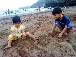 foto anak bermain pasir di pantai