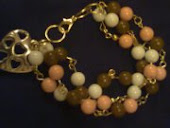 pulseira dourada c 3 voltas em tom de laranja,beje e marrom