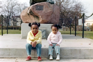 photo of two young girls sitting on the concrete slab of a statue