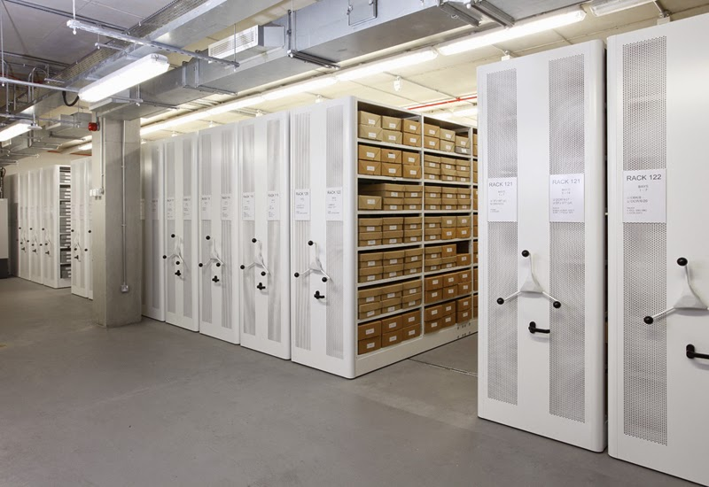 A brightly lit basment room containing ranks of roller Archive shelving.  On an open shelf we can see dozens of brown cardboard boxes all labeled.