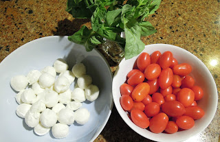 Pictue of the ingredients for a caprese salad - tomatoes, mozzarella cheese, and basil