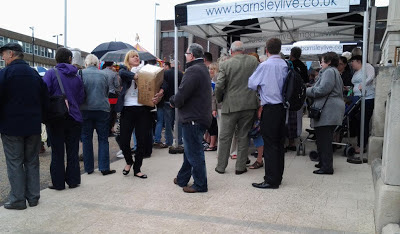 A group of people, mostly facing left stood on a slope, a black and white gazebo labelled Barnsley Live and a woman struggling with a large cardboard box.