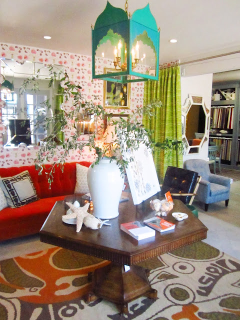 foyer in Harbinger showroom with large tile mirror, green curtain, red sofa, floor to ceiling wall paper on one wall, a hexagon table holding assorted odds and ends and a large rug