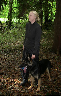 Dog and handler standing in the wood looking relaxed