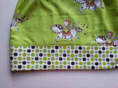 a detail shot of the border and hem of a lime green skirt