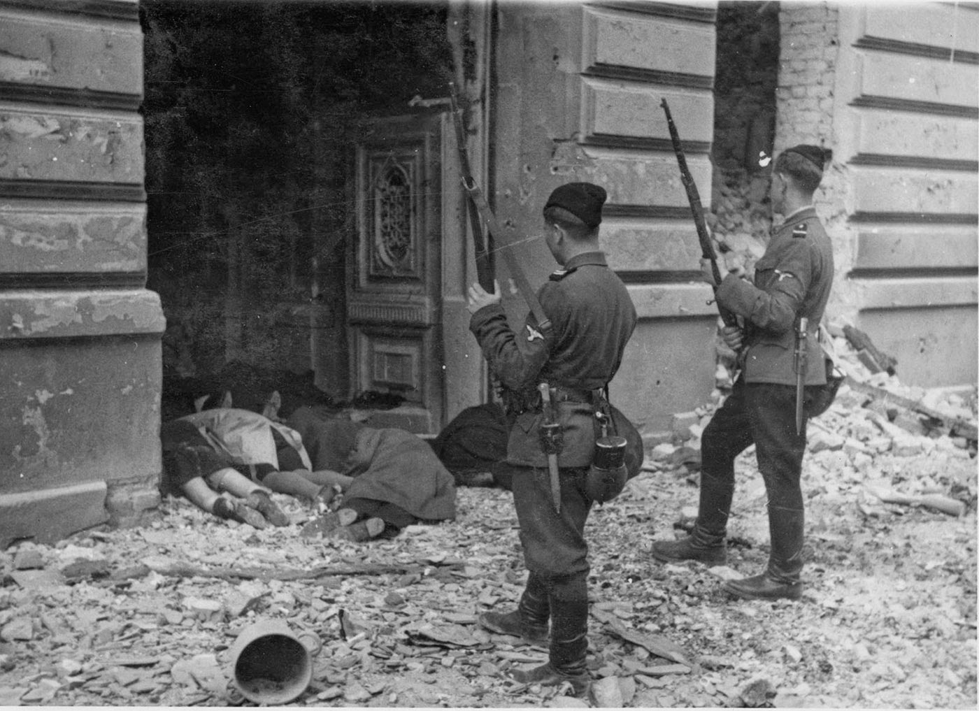 Two Ukrainian Askaris peer into a doorway past the bodies of Jews killed during the suppression of the Warsaw Ghetto Uprising, 1943.