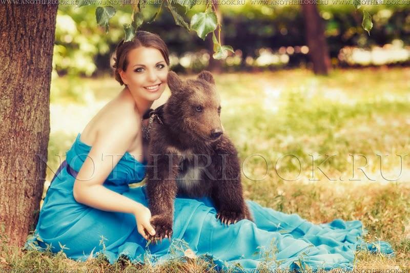 Девушка держит медведя за лапу