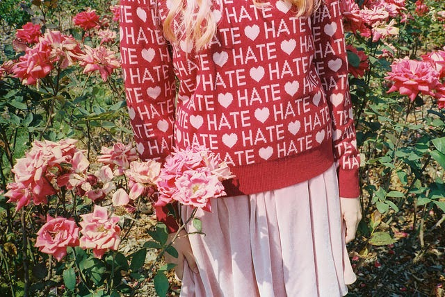 "Image of a girl in a sweater covered in the word ""HATE"" separated by hearts."