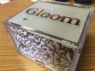 "Closed box with colored ""Gloom"" logo sticker on top and black and white scrollwork scrapbook paper lining the inside sides of box"