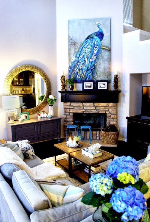 closer look to the living room area shows a cool blue peacock above exposed brick fireplace