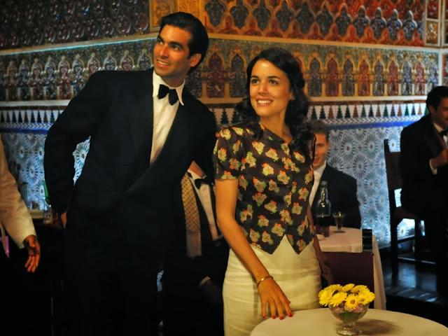 Sira Quiroga blusa flores y falda blanca lápiz y Ramiro con esmoquin. El tiempo entre costuras. Capítulo 1.