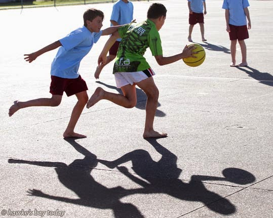 L-R: Justin Linton, Treyah Kingi-Taukamo, Tamatea Intermediate School, Napier, playing basketball barefooted, outside in the gloriously warm winter weather, for which Hawke's Bay is so well known. photograph