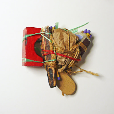 This brooch has been assembled out of small wooden toy parts, matches, paper and string, and looks to create the impression that this piece is soon to be set alight.