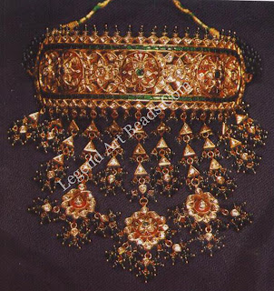 "Adiya (""of the rich"") necklace, Jaipur  One of the most lavish examples of the jeweller's repertoire, the adiya necklace features a rigid choker from which flows a cascade of set gems. In this fine example, we see the kundan work and brilliant red enamel of Jaipur."