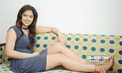 Charming tamil actress NIKISHA PATEL in sort dress showing smooth legs looking sexy and hot sitting on couch silky long hair beautiful indian girl