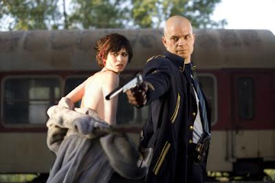 Escena de la película Hitman donde se ve un tren al fondo y el Agente 47 protegiendo a la chica.