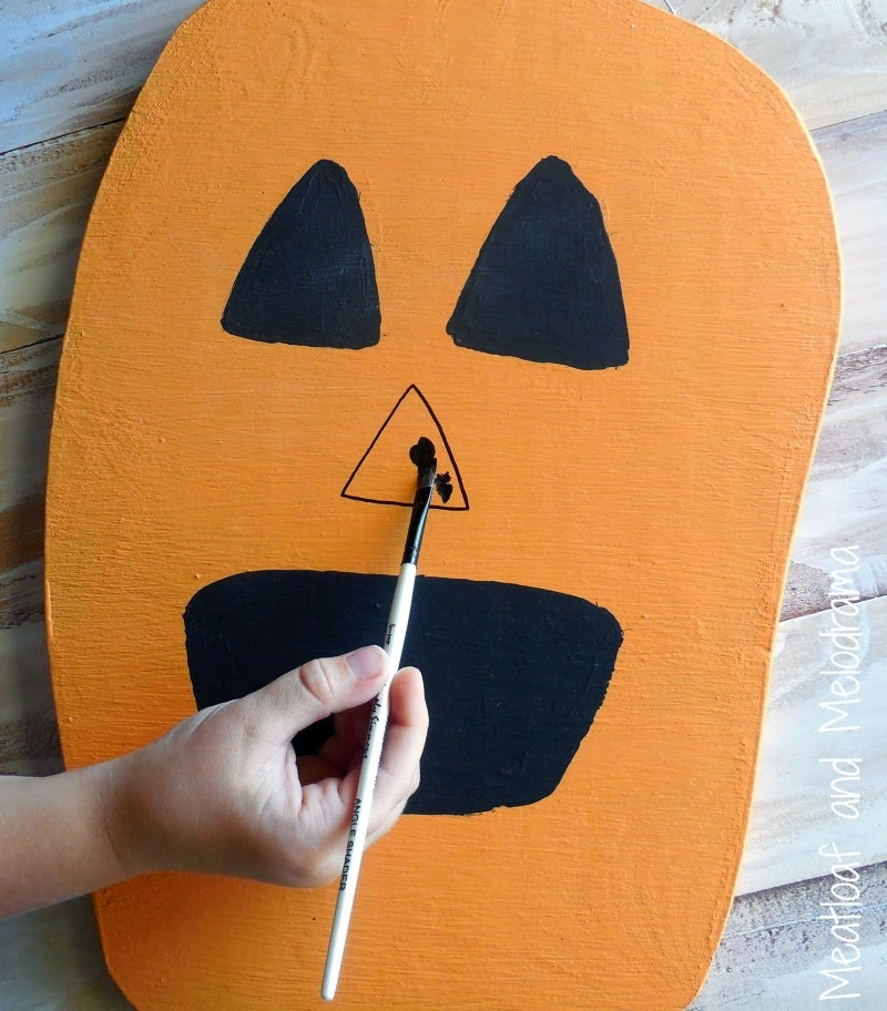 painting face on wood pumpkin