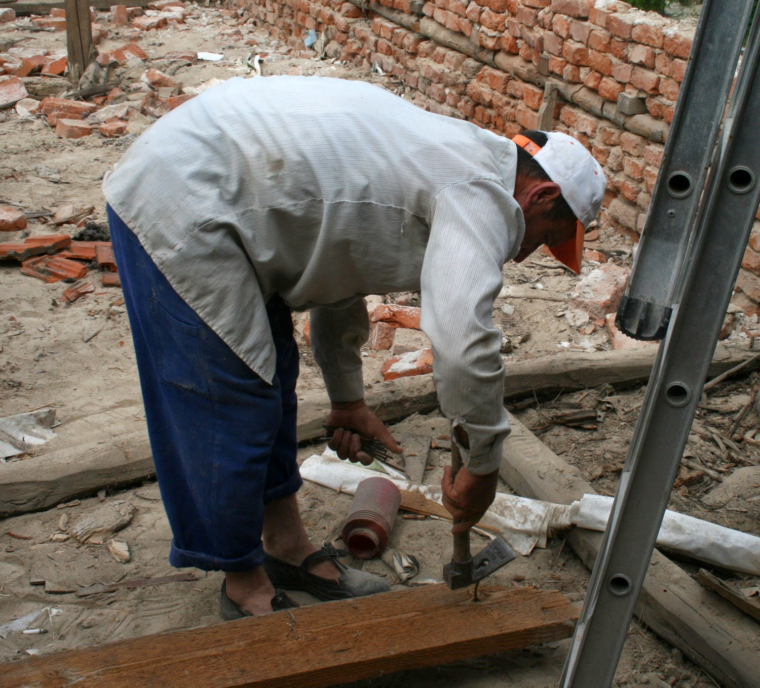 Bekir removing nails from a beam