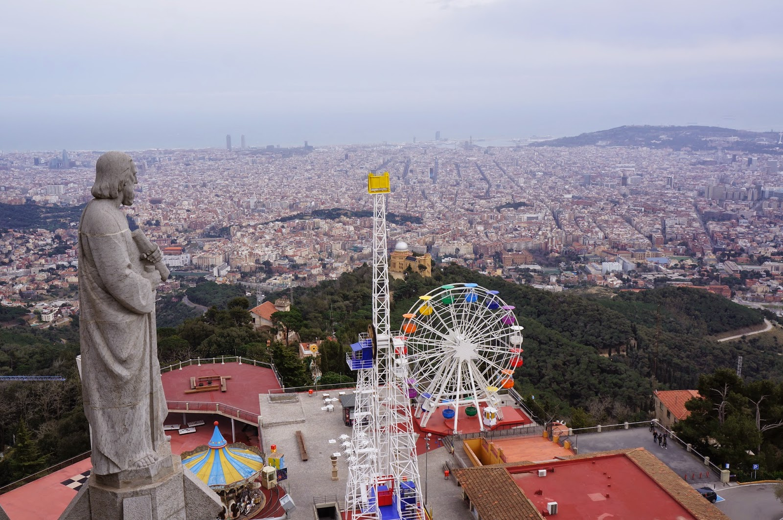 Statue from the cathedral overlooking the Tibidabo amusement park and Barcelona Spain