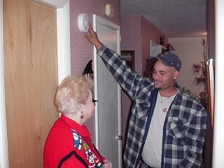 A family member showing the use of fire detector.