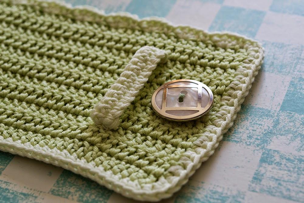 Funda verde de ganchillo para taza con botón