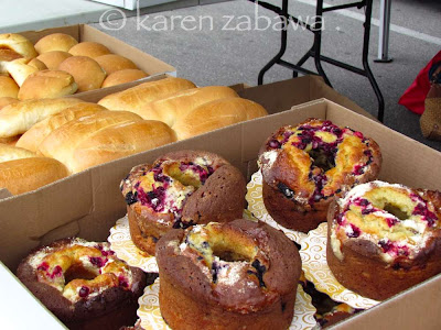 Buns, pizza, muffins and coffee cakes tempting wares at Port Credit famers market.