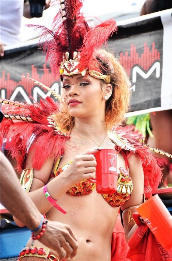 Rihanna returns home to Barbados for the Kadooment Day Parade. The sexy songstress showed off her amazing bod in a red skimpy bikini ensemble. Even though her signature red locks were missing in action, in its place the singer wore red decorative feathers as head gear.