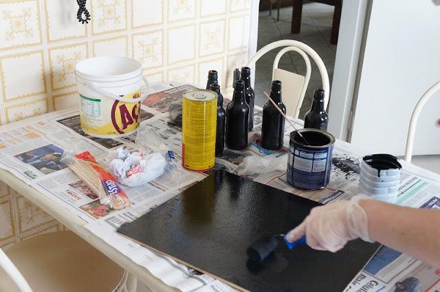 Pintando um dos lados do pedaço de MDF com a tinta lousa