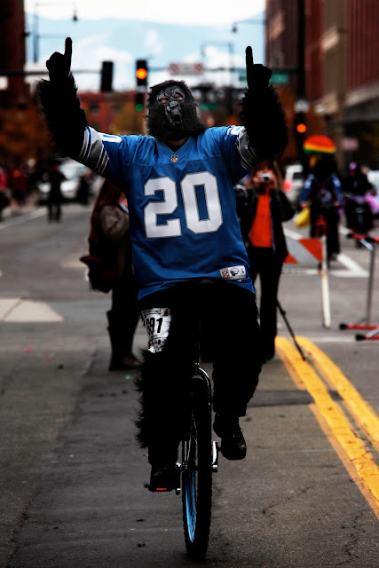 A gorilla mask and a Barry Sanders jersey on a unicycle in downtown Denver.