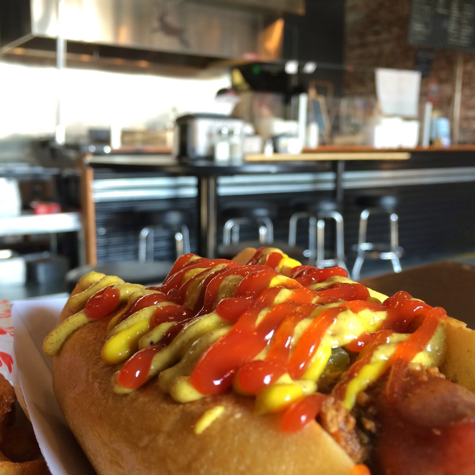 Beef Frank topped with Dill Pickle Relish, Chili, and the most beautiful array of Ketchup and Mustard you've ever seen