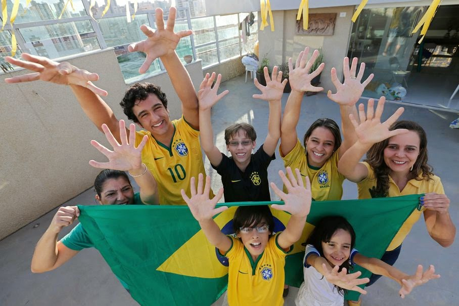 Members of the Silva family, back row, from left, Silvia Santos, Joao de Assis, Pedro de Assis, Ana Carolina Santos and Silvana Santos, front row, Bernardo de Assis, left, and Maria Morena Santos, pose for a photo in their home to show that they each have six fingers on each of their hands, in Brasilia, Brazil, Thursday, June 19, 2014. The family was born with an extra digit on each hand as a result of a genetic condition known as polydactyly.