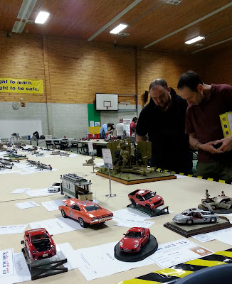 Two men looking at a display of scale model cars.